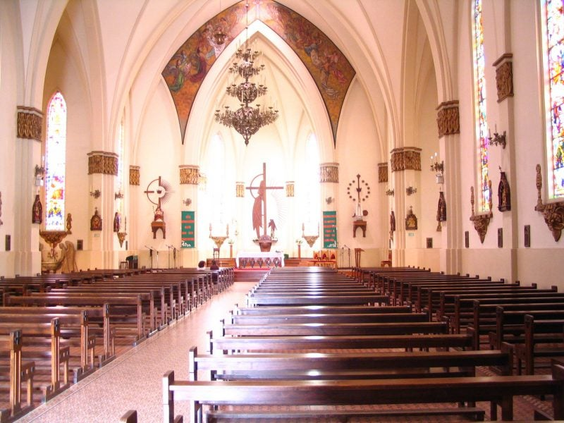 empty pews at a church with a large cross and stained glass windows