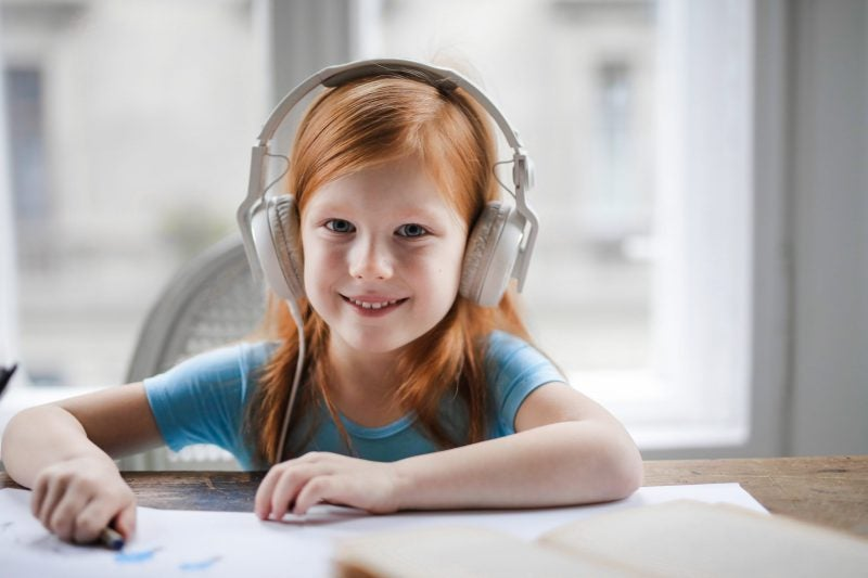 Photo of girl wearing white headphones and smiling