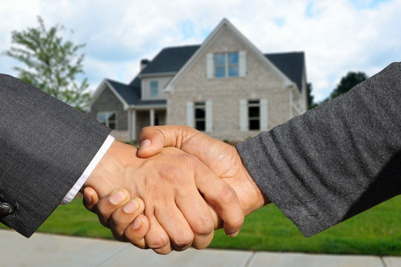 Men shaking hands in front of a house