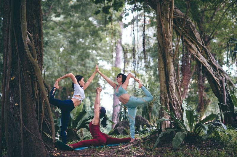 3 women do a trio yoga pose in the forest