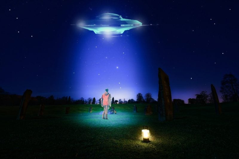 man looking at ufo at night