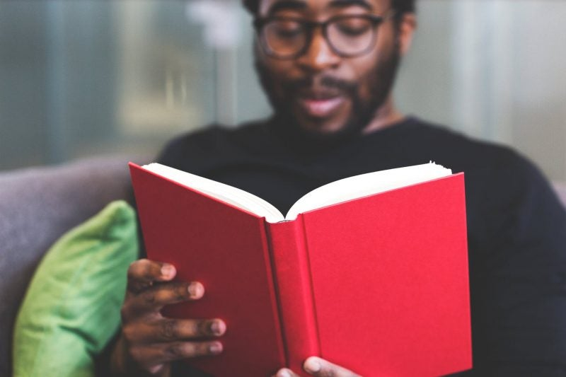 black man reading red book