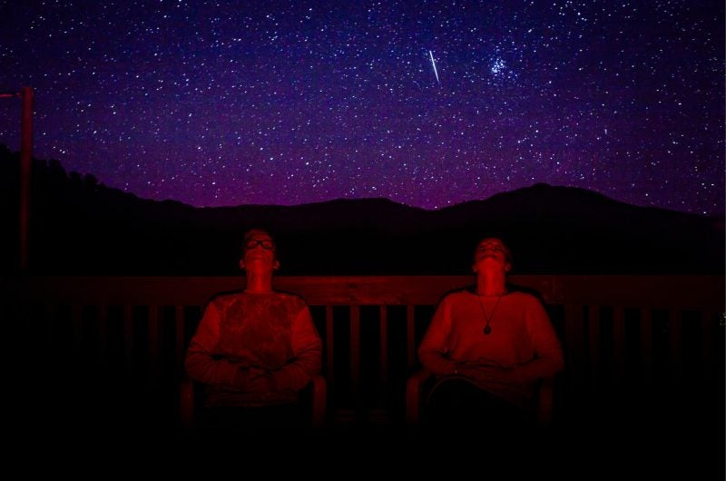 two men on hill gazing at stars