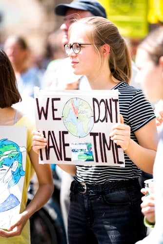 girl iwth protest sign we don't have time