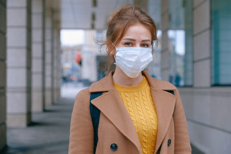 Woman wearing disposable face mask in public