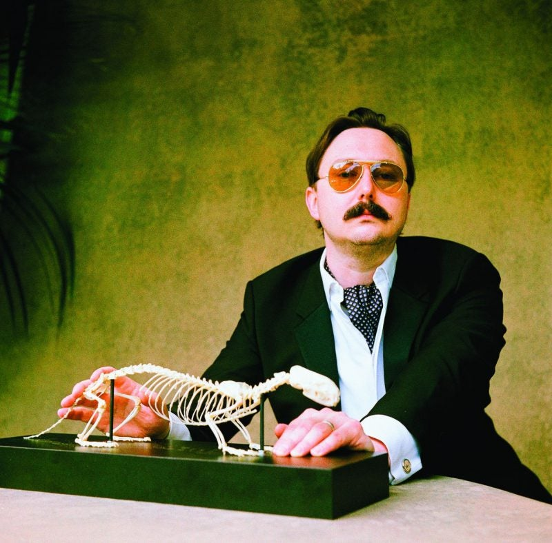 John Hodgman poses with baby dinosaur skeleton in a kerchief