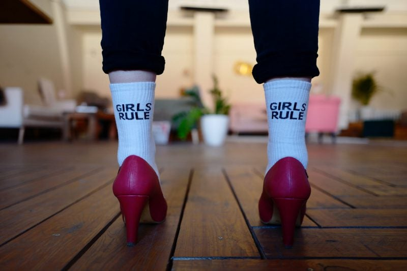 Woman wearing pink high heels and white girls rule printed socks